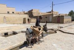 人和驴在Kharanagh村庄,伊朗 库存照片