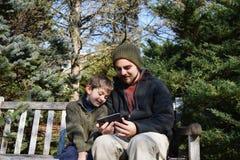 年轻人和年轻男孩分享在长凳的电话 库存图片