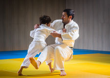 人和年轻男孩训练柔道摔 免版税库存照片