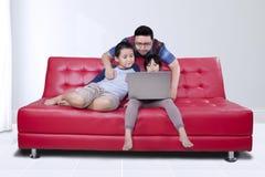 年轻人和他的使用膝上型计算机的孩子 免版税库存图片