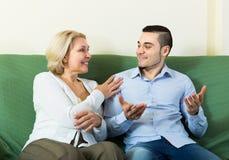 年轻人和年迈的妇女谈话室内 库存照片