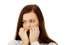 年轻人咬住她的钉子的被注重的妇女 免版税库存照片