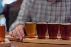 人品尝从飞行的工艺啤酒 免版税库存图片