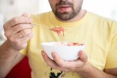 人品尝草莓酸奶、健康食物和生活方式 图库摄影