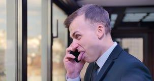 人商人在电话里说并且做面孔,显示他的舌头,在对话者的嘲笑 假装,嘲笑 股票视频