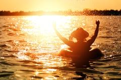 人商品帽子和他在游泳管在水中 他是手做水飞溅 库存图片