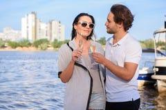人喝与他的夫妇的香槟在海滩 免版税库存照片