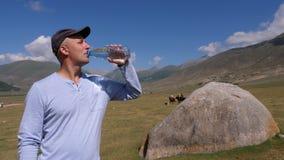 人喝从瓶的水在远足山、小山和高地背景 股票视频
