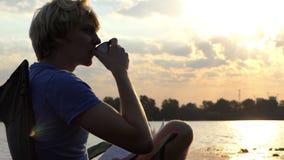 人喝在一把折叠椅的咖啡与他的笔记薄在日落在Slo Mo 股票录像