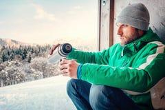 人喝开放冬天空气的一个热的饮料工作者ot旅客 免版税库存照片