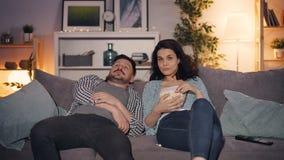 人回家看着电视和谈话与一起吃玉米花的妻子 股票视频
