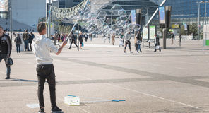 人在一个中心广场中间做巨型泡影 免版税图库摄影