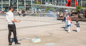 人在一个中心广场中间做巨型泡影 免版税库存图片