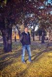 人在一个公园站立,在五颜六色的落的叶子中 库存照片