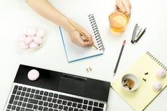 人在一个空的笔记本拿着一个杯子用茶并且写 免版税图库摄影