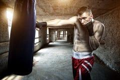 年轻人在一个老大厦的拳击锻炼 库存图片