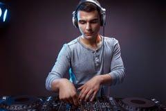 年轻人在一台dj ` s搅拌器的戏剧音乐在演播室 库存图片