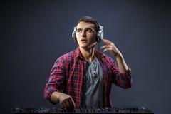 年轻人在一台dj ` s搅拌器的戏剧音乐在演播室 免版税库存图片