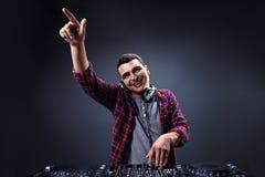 年轻人在一台dj ` s搅拌器的戏剧音乐在演播室 免版税库存照片