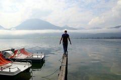 年轻人在一座桥梁走有在湖的近看法到在多云天气的山 免版税库存照片