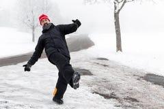 人在一条冰冷的路滑倒 免版税库存照片