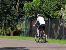 人在一辆自行车的后面轮子乘坐在柏油路的在村庄反对橄榄球场的背景 生态学 免版税库存图片