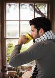 人在与杯子的秋天由窗口在家 免版税库存照片