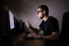 人在个人计算机附近的用途电话 库存照片
