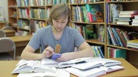 人在书和查寻中的一个图书馆里对于关于他的智能手机的信息 影视素材