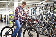 人在买前检查自行车在商店 免版税库存图片