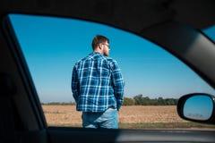 人在从汽车的一个路视图站立 免版税库存照片