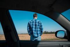 人在从汽车的一个路视图站立 免版税库存图片