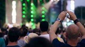 人在他的在音乐节的智能手机做有音乐会的录影 股票录像