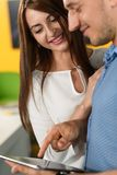 人在他的妇女的片剂新的汽车显示 免版税库存照片