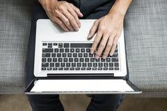 人在他的家使用在沙发的膝上型计算机 大角度看法,在h的工作 免版税库存图片