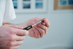 人在他的手上拿着一把螺丝刀-白色皮肤,黑和黄色螺丝刀 大师在家运作 库存图片