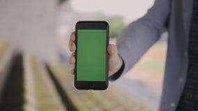 人在他的手上拿着有室外一个绿色的屏幕的一个智能手机 影视素材