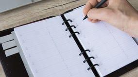 人在他的笔记本写某事 顶视图,平的位置 空的启发人笔记本 一个人以空 库存照片
