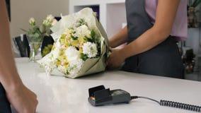 人在付款终端,手特写镜头买在花店的花束支付由卡片 股票视频