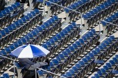 人在伞下在体育场内 免版税库存照片