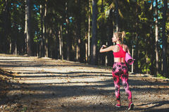 年轻人在佩带巧妙的手表和拿着瑜伽席子的森林里适合了运动妇女,轻易地胜过照相机 库存照片