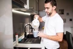 人在倒一个杯子从一个玻璃罐的热的咖啡的厨房里 吃早餐早晨 免版税库存照片