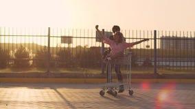 人在停车场滚动台车的可爱的少妇超级市场在日落 慢的行动 股票视频