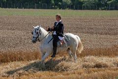 人在全国服装在马背上穿戴了,乘坐通过麦田在麦子收获期间 免版税库存照片