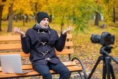人在公园坐在与一台膝上型计算机的一条长凳在照相机前面在三脚架和失望用手 库存图片