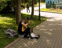 人在公园弹吉他,在边路 免版税库存照片