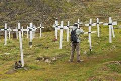 人在公墓拍白色十字架的照片在朗伊尔城,挪威 库存照片