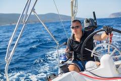 年轻人在公海操纵一条航行游艇小船 体育运动 免版税库存照片