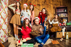 人在六名妇女陪同下在有圣诞节的d屋子里 库存照片