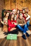 人在六名妇女陪同下在有圣诞节的d屋子里 免版税库存照片